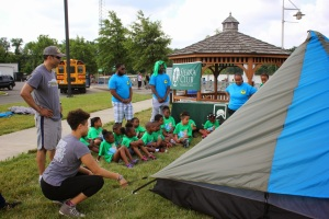 Members of NOLS Expedition Denali teach young campers how to pitch a tent